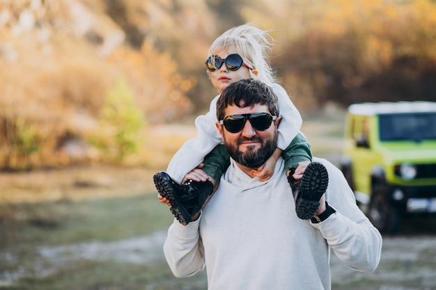 Giovane padre alla moda con la figlia piccola seduta sulle spalle