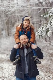 Giovane padre barbuto ed il piccolo figlio sulla camminata nella foresta di inverno. il ragazzo si siede nelle spalle dell'uomo. vacanze di natale