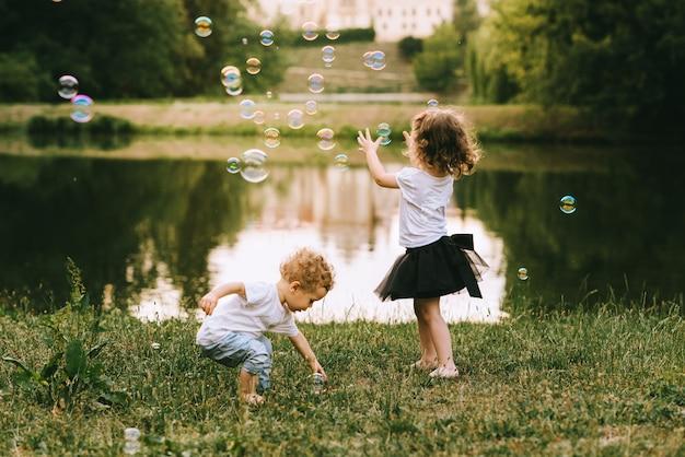 Giovane padre bello e bella madre in natura soleggiata di estate che giocano con i loro piccoli bambini svegli