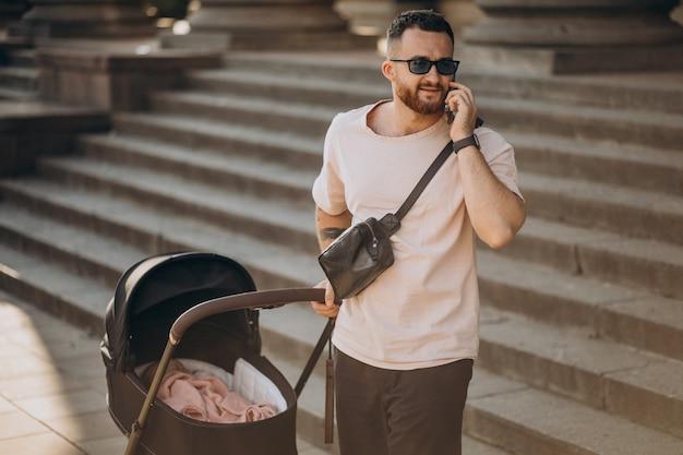 Giovane padre che cammina fuori con il suo bambino in una carrozzina