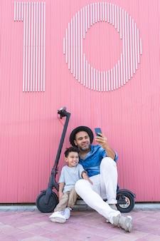 Giovane padre che prende un selfie con suo figlio su un motorino elettrico.