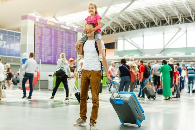 Giovane padre che tiene bambina sul suo collo mentre legge le informazioni di partenza sull'orario elettronico in aeroporto