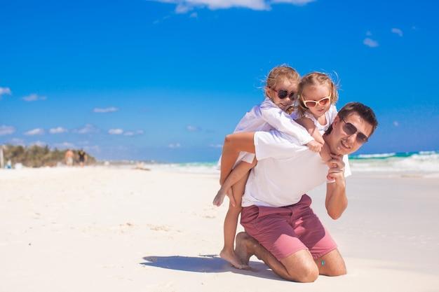 Giovane padre felice e piccole figlie divertendosi sulla spiaggia bianca nel giorno soleggiato