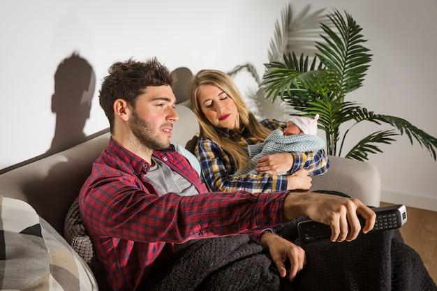 Giovane padre guardando la tv mentre madre con il bambino dorme