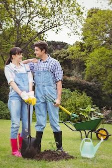 Giovane pala della tenuta delle coppie e forcella di spading in giardino