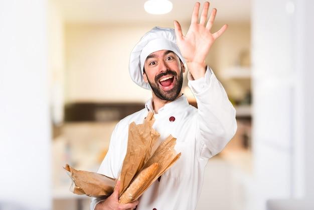 Giovane panettiere in possesso di un po 'di pane e saluto in cucina