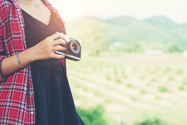 Giovane pantaloni a vita bassa fotografo della donna in possesso di un macchina fotografica d'epoca.
