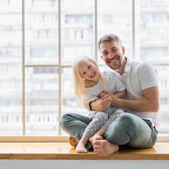 Giovane papà che tiene sua figlia di 3,5 anni mentre era seduto sul davanzale della finestra.