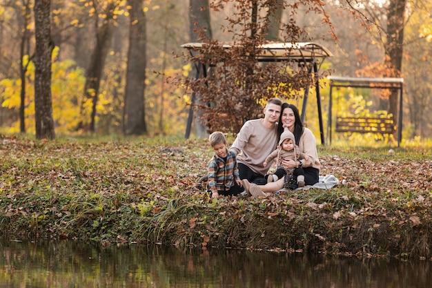 Giovane papà e mamma con la neonata e il piccolo figlio che hanno divertimento sulla coperta vicino allo stagno nel parco di autunno