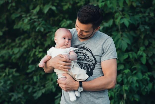 Giovane papà felice con un figlio neonato figlio nelle mani