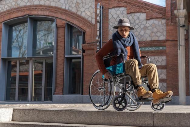 Giovane paralizzato in una sedia a rotelle frustrato davanti ad alcune scale