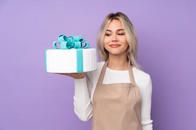Giovane pasticcere che tiene una grande torta sopra la parete viola