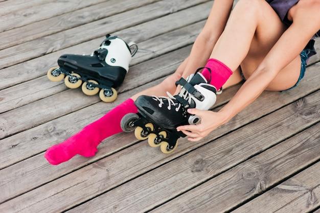 Giovane pattinatore felice della donna che si siede sui bordi di legno e che prova sui pattini di rullo all'aperto. stile di vita sportivo