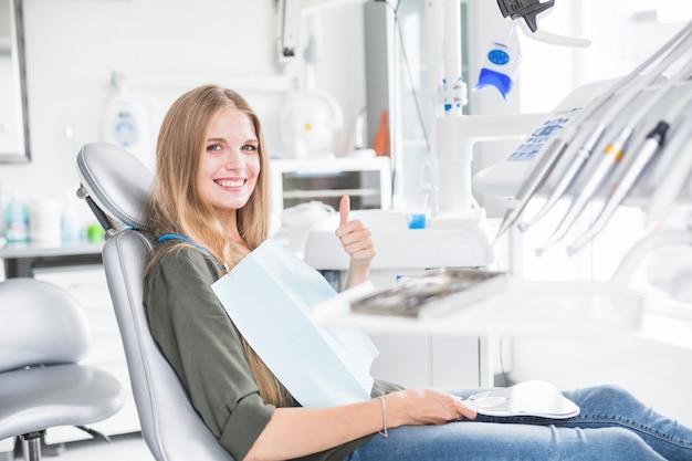 Giovane paziente femminile felice che si siede sulla sedia dentaria che gesturing segno giusto