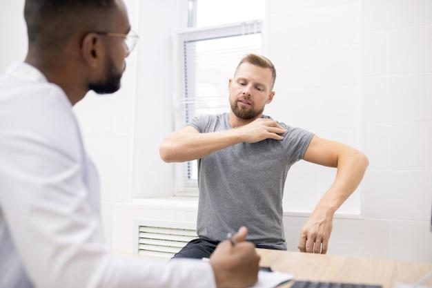 Giovane paziente malato in abbigliamento casual che tocca la sua spalla mentre mostra al medico dove fa male durante la consultazione medica