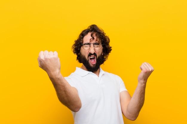 Giovane pazzo che grida trionfalmente, sembrando vincitore eccitato, felice e sorpreso, celebrando contro la parete gialla