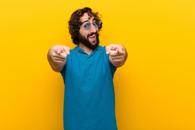 Giovane pazzo che si sente felice e fiducioso, indicando la fotocamera con entrambe le mani e ridendo, scegliendo te contro il muro arancione