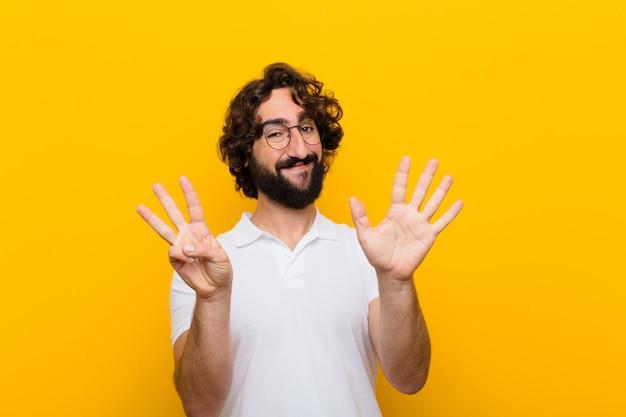 Giovane pazzo che sorride e che sembra amichevole, mostrando numero otto o ottavo con la mano in avanti, contando il muro giallo