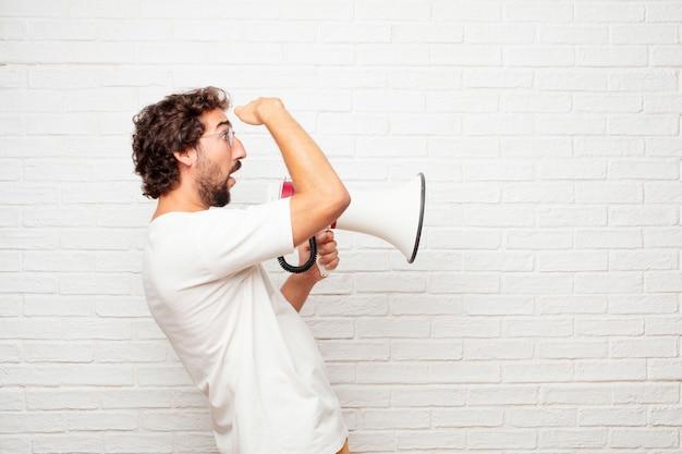 Giovane pazzo con un megafono contro il muro di mattoni.
