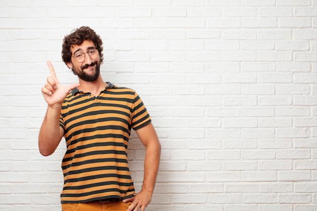 Giovane pazzo o uomo sciocco che gesturing e che esprime le emozioni contro il fondo del muro di mattoni