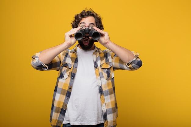 Giovane pazzo pazzo pazzo posa con un binocolo
