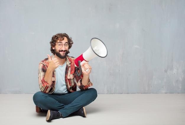 Giovane pazzo pazzo pazzo posa con un megafono.