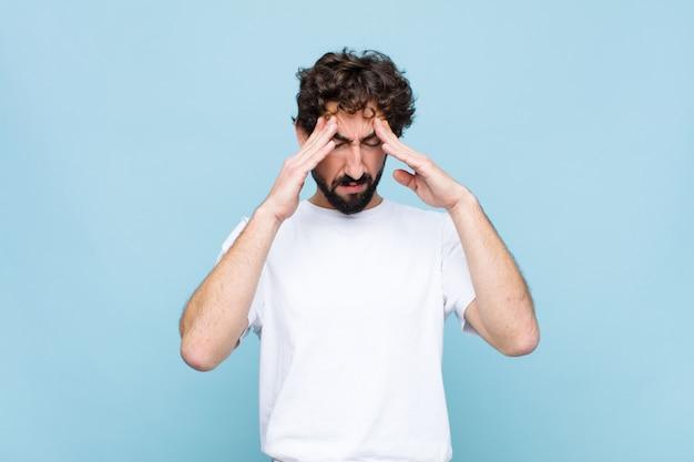 Giovane pazzo uomo barbuto che sembra stressato e frustrato, che lavora sotto pressione con un mal di testa e turbato da problemi contro il muro