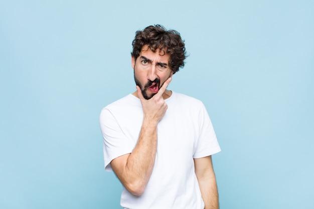 Giovane pazzo uomo barbuto con la bocca e gli occhi spalancati e la mano sul mento, sentendosi spiacevolmente scioccato, dicendo cosa o wow sul muro