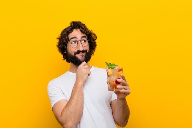 Giovane pazzo uomo barbuto con un cocktail. concetto turistico