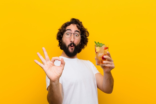 Giovane pazzo uomo barbuto con un cocktail. turista
