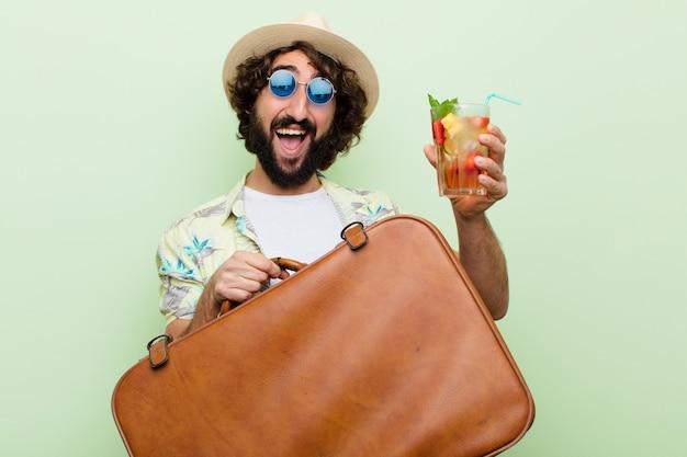 Giovane pazzo uomo barbuto con un cocktail. viaggio