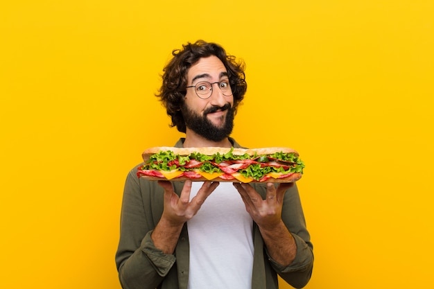 Giovane pazzo uomo barbuto con un panino gigante.