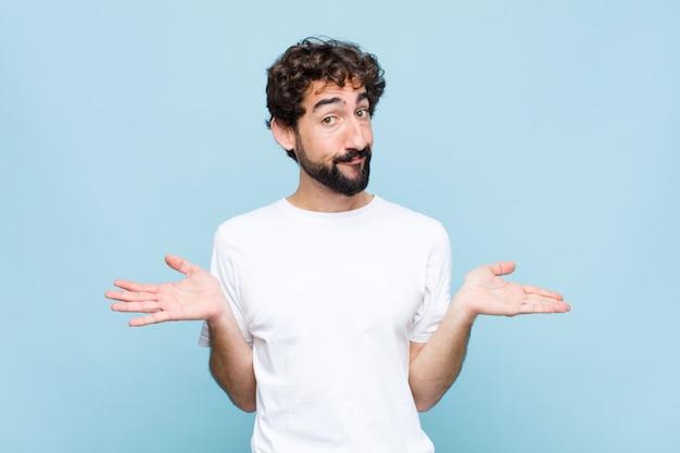 Giovane pazzo uomo barbuto sentirsi perplesso e confuso, incerto sulla risposta o decisione corretta, cercando di fare una scelta contro la parete piatta