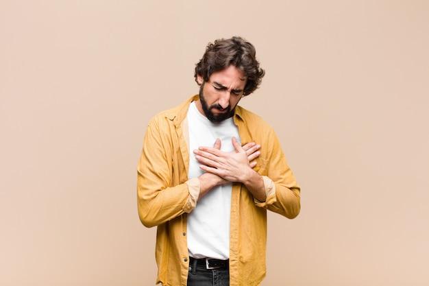 Giovane pazzo uomo freddo che sembra triste, ferito e con il cuore spezzato, tenendo entrambe le mani vicino al cuore, piangendo e sentendosi depresso contro la parete piatta