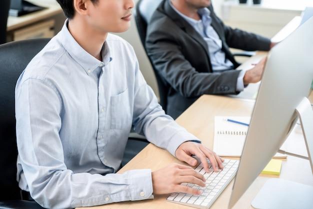 Giovane personale di ufficio maschio che lavora al computer