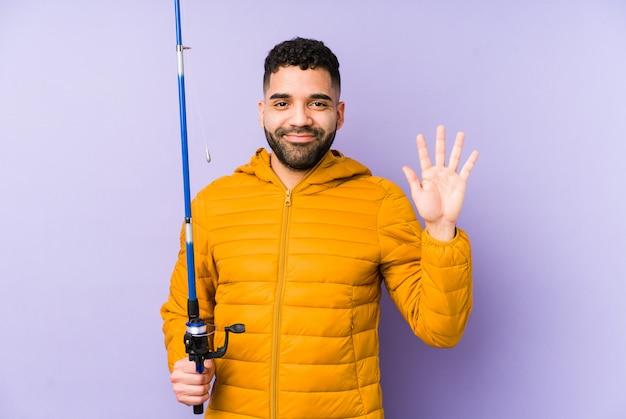 Giovane pescatore latino che tiene un'asta e che mostra numero cinque con le dita