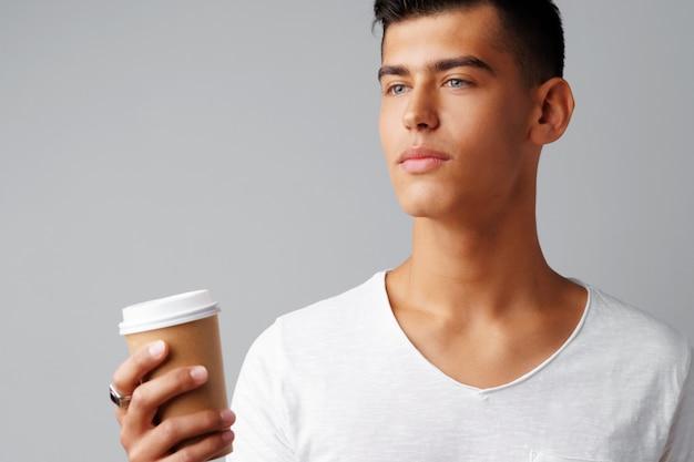 Giovane piacevole del brunette che tiene una tazza di caffè sopra una priorità bassa grigia