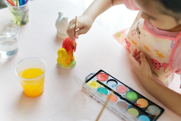 Giovane piccola ragazza asiatica che dipinge le bambole animali del gesso nella classe della pittura a casa.