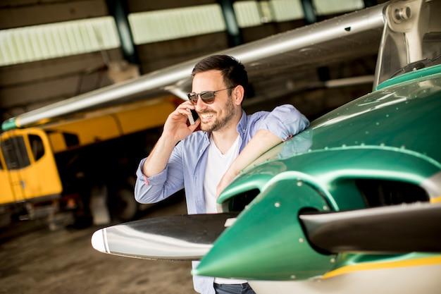 Giovane pilota bello che controlla aeroplano nel capannone e che per mezzo del telefono cellulare