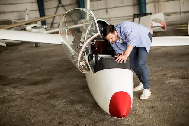 Giovane pilota che controlla l'aeroplano nell'hangar
