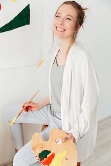 Giovane pittore caucasico felice di signora che si siede all'area di lavoro