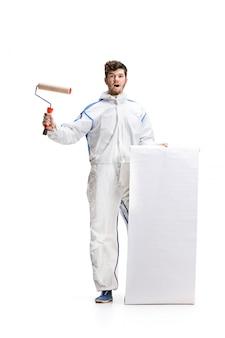 Giovane pittura maschio del decoratore con un rullo di pittura isolato sulla parete bianca.
