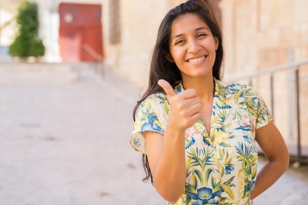 Giovane pollice indiano della donna in su nella via