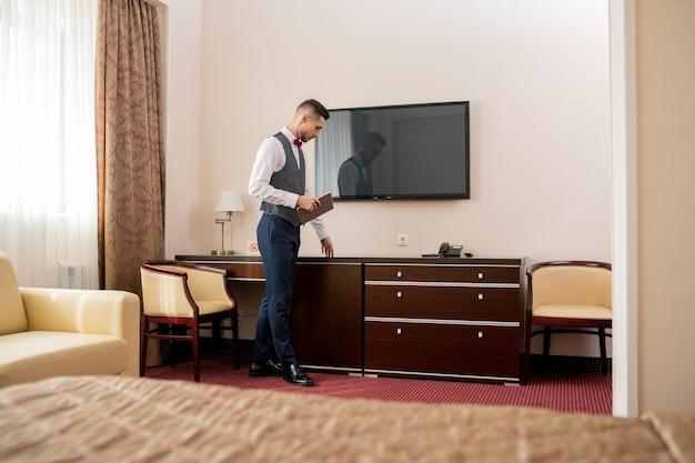 Giovane portiere di hotel elegante con tavoletta digitale che tocca un mobile in legno durante il lavoro