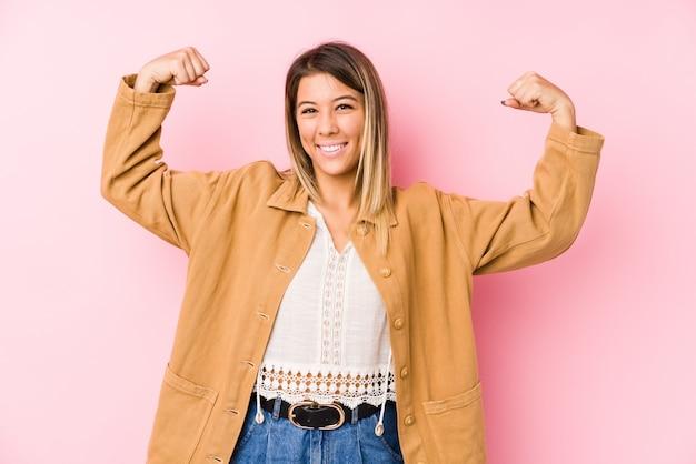 Giovane posa caucasica della donna isolata mostrando il gesto di forza con le armi, simbolo di potere femminile