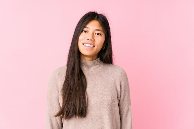 Giovane posa cinese della donna isolata felice, sorridente e allegro.