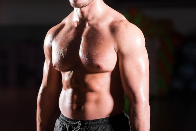 Giovane posa muscolare attraente del culturista dell'uomo