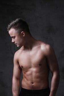 Giovane posa sexy senza camicia dell'uomo