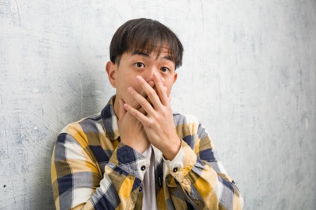 Giovane primo piano cinese del fronte dell'uomo sorpreso e colpito