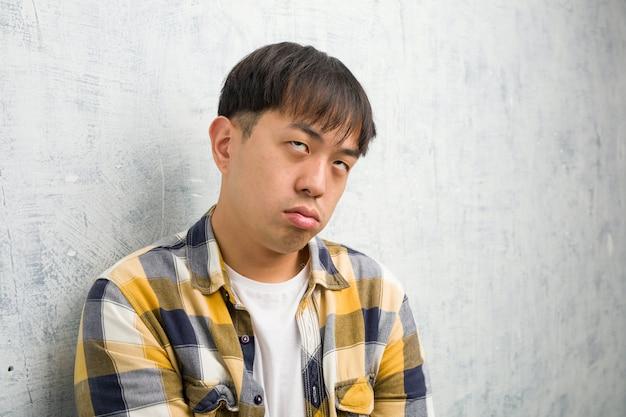 Giovane primo piano cinese del fronte dell'uomo stanco e annoiato